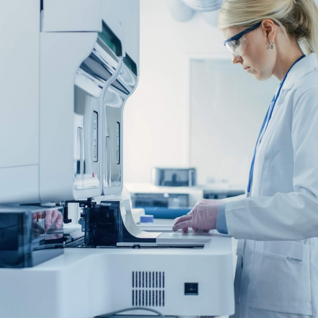 Female Research Scientist Putting Test Tubes with Blood Samples into Analyzer Medical Machine. Scientist Works with Modern Medical Equipment in Pharmaceutical Laboratory.